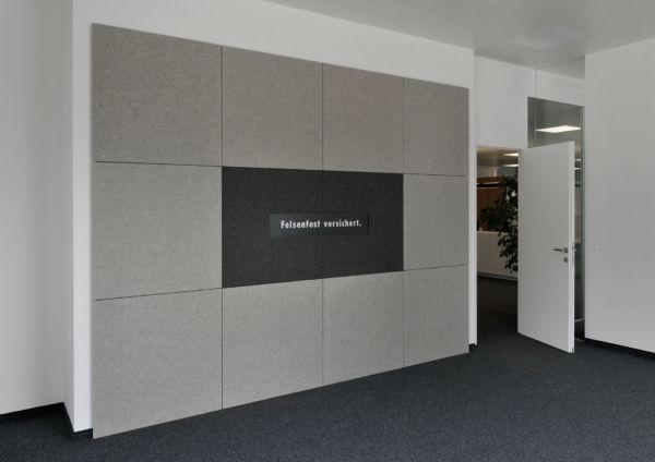Eine Bürowand, an der Akustikplatten kreativ in einem großen Rechteck platziert wurden.