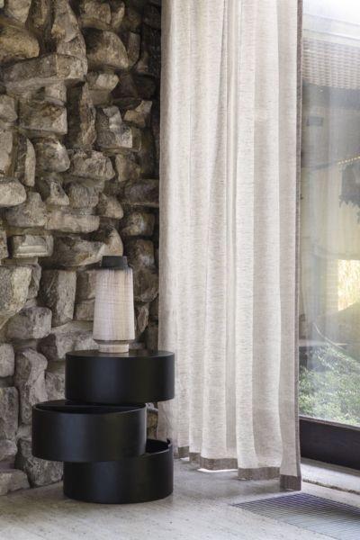 Ein beiger, dünner Vorhang ziert ein Fenster.