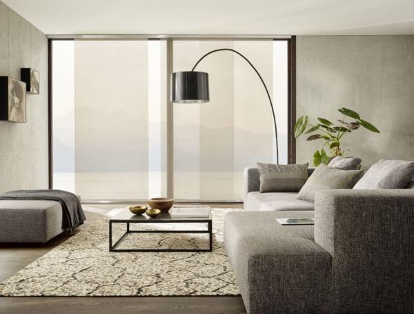 Beige Flächenvorhänge zieren die Fenster eines modernen Wohnzimmers.