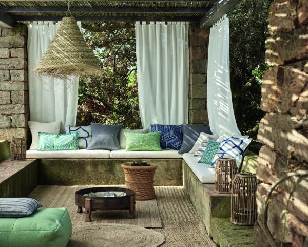 Outdoor-Wohnzimmer, das von weißen Vorhängen umrahmt wird.