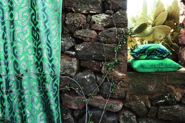 Ein türkis-gemusterter Vorhang und Kissen an einer Steinmauer.