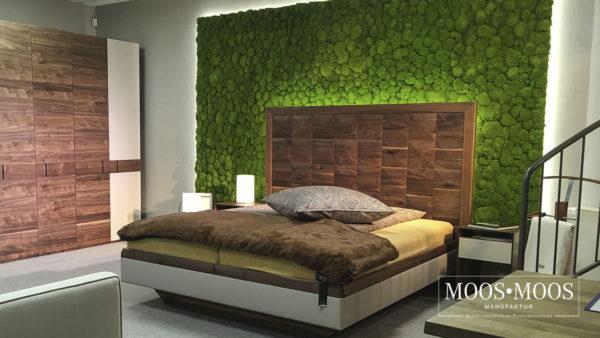 Ein Schlafzimmer, das mit einer Mooswand hinter dem Bett ausgestattet wurde.
