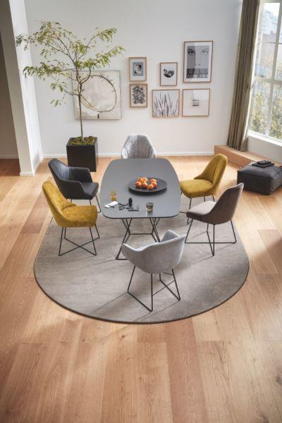 Ein heller Essraum, der von einem halbrunden, grauen Teppich unter dem Tisch ausgefüllt wird.