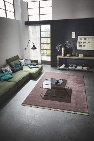 Ein modern eingerichteter Wohnraum mit einem großen, weinroten Fransenteppich.