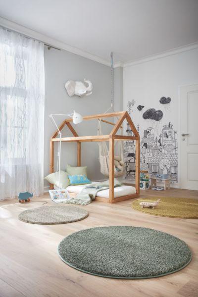 Drei bunte, runde Teppiche schmücken den Boden eines Kinderzimmers.